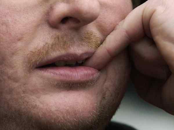 грызет ногти мужчина