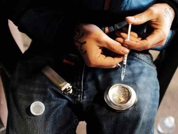 парень прикотавливает наркоту