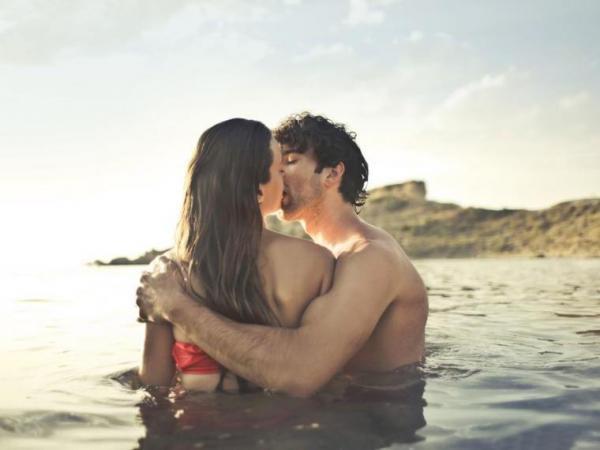Парень держит девушку в море