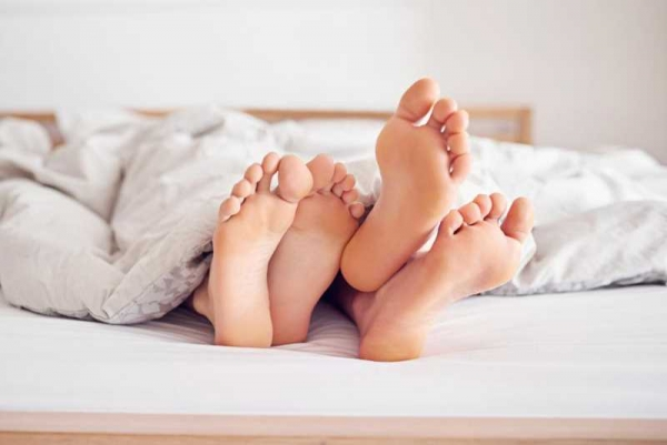 Фото. Две пары ног в постели