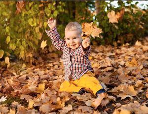 мальчик среди упавшей листвы