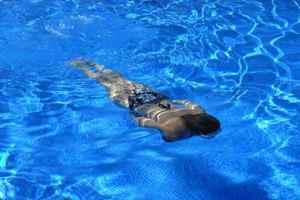 девушка плывет под водой в бассейне