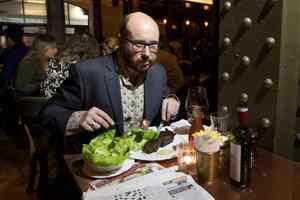 мужчина ест за столом