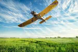 желтый самолет над зеленым полем