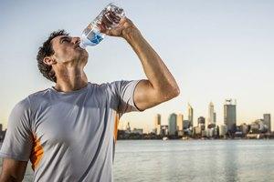 мужчина пьет воду из бутылки