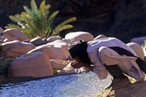 мальчик пьет воду из реки