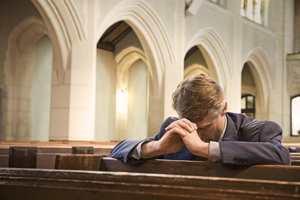 парень молится в церкви