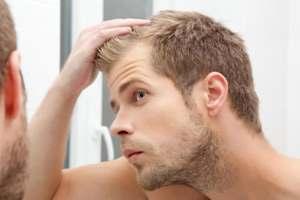 парень смотрит на выпадающие волосы